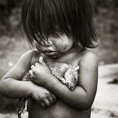 A poor homeless girl holding a dead rat...an image that seems simple but in fact is more powerful in the emotion it conveys.