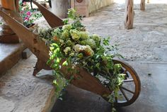 Use elements around your wedding venue to hold floral displays like this wooden wheelbarrow