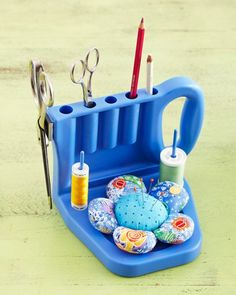 The Grabbit Tool Caddy, with its handle on the side, keeps hand- or machine-sewing supplies corralled. A strong magnet grabs a pair of scissors, two thread spindles hold spools and bobbins, five cylinders stash tools vertically, and a tray cradles a magnetic pincusion.