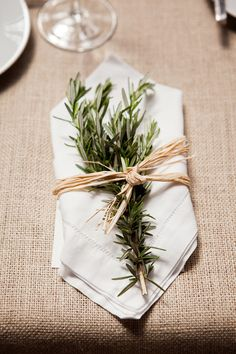 Herbs/olive leaves on table linens. Photography By / http://firstcomeslovephoto.com