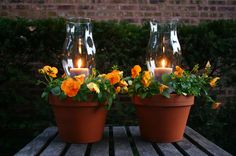 Clay pots turned into lanterns with candles and flowers for patio or outdoor areas.