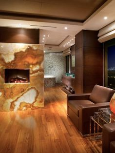 This backlit onyx fireplace showcases the rich colors of the stone. The fireplace serves as a bridge between the master bedroom and bathroom. Design by Pepe Calderin; photography by Barry Grossman