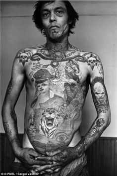 This prisoner's tattoos display his anger and bitterness towards Communist power; the tattoos on the face signify that he never expects to go free
