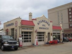 """""""The gas station was built by Standard Oil Company of Indiana in 1927-28 and had a one garage bay attached. It was built with glazed brick on all walls and red tile on the roof. In 1935-36 a second garage bay was added. It was in operation as a gas station until 1979, in 1985 the library bought the property for a future parking area. In 1991, Don Stein, a local business man and auto collector offered to restore the gas station and was finished later that year."""