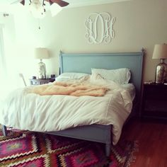 Blue bed frame, neutral bedding, bright rug, and his and hers Monogram
