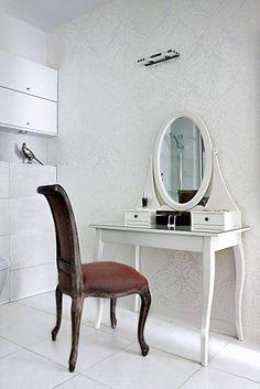 Tym razem kobiecy kąciki gospodarze urządzili w łazience. Lekka biała toaletka wtapia się w tło - ścianę pokrytą elegancką tapetą.