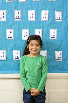Young female student standing in front of a board of flash cards. Vertically framed shot.   Awesome picture!