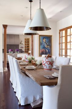 Modern farmhouse dining. Love the white slip covered chairs with the rustic dining table.