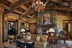 Fab greatroom with two seating areas.  In the corner is a library and music room.  I like the arched beams, as well as the reclaimed barnwood ceiling.  SBC Builders, Bozeman, Montana