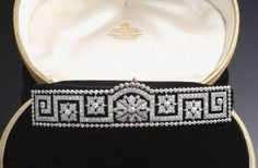 An early art deco bandeau tiara from the Edwardian period, circa 1911. Featuring a series of Greek Key geometric lines, encasing five stylised floral motifs, and surrounded by a line of circular diamonds.