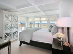 HGTV: A spacious master bedroom boasts large windows and glass doors which open onto a private luxurious beach, an opulent white bed, and a glass hutch.