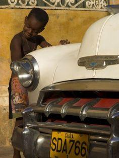 Young Boy Drumming on Old American Car's Bonnet,Trinidad, Sancti Spiritus Province, Cuba Photographic Print