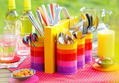 Nette Idee für eine Gartenparty: Konservendosen mit Plakafarbe bunt anmalen und als Behälter für Besteck, Servietten und Strohhalme nutzen.