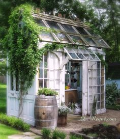 Donna Reyne's adorable gardening shed with sliding doors. Sweet Autumn clematis is growing up the side. ~ dreyne.com