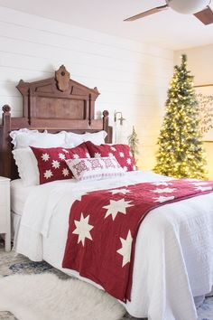 A master bedroom decorated for Christmas using traditional red, white and green. Vintage Eastlake headboard and a brightly lit tree in the corner.