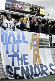 PENN STATE – FANS AND ALUMNI – Penn State students huddle together to stay warm above a banner honoring the football seniors during the Saturday, November 23, 2013 game against Nebraska at Beaver Stadium. ABBY DREY — CDT photo
