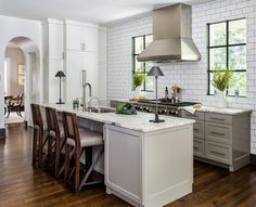 Light gray kitchen cleverly design with no upper cabinets boasts a stainless steel kitchen hood flanked by black windows framed by white subway backsplash tiles accented with dark gray grout mounted above gray shaker cabinets positioned on either side of a stainless steel oven range.