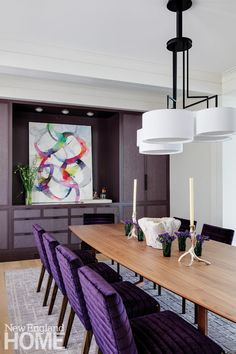 The bright purple upholstery on the dining room chairs creates a visual link to a lively mixed-media work by artist Doug Kennedy.
