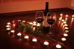 Romance romantic setting of two wine glasses and one red rose with lighted candles in a shape on the table