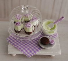 Miniature Cupcakes With Purple Roses On A Pretty Covered Ribbed Glass Cake Stand, A Bowl Of Icing, A Cupcake, A Rose, And A White Tray