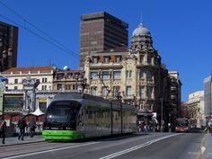 https://flic.kr/p/KYXhYF | Fragmento | De un momento cotidiano en la ciudad. Entre el movimiento de los peatones y el transporte público que recorre esas calles llenas de una variedad exquisita de edificios.  Bilbao, España.