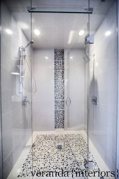 Pebble floor and back-splash, modern tile, frame-less glass door and panels, narrow dual shower.