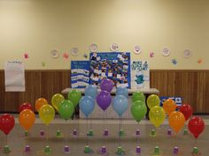Our rainbow bridge with the girls WOW Journey displayed behind it. We poked the balloon ribbon through the colorful paper cups and taped the ribbon onto the floor... because that many balloon weights can get pricey.                                                                                                                                                                                 More
