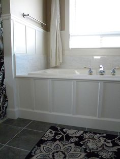 updated 90's bathtub in one weekend with less than $200, using marble and paneling over the existing old tiles.