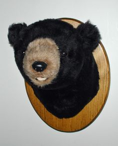 """Plush Black Bear Head """"Harry"""" Small Plaque Mount. Our little bears all love celebrating. They enjoy wearing headbands, hats, bandannas, and bow ties! As with all our smaller bears, Harry's fur is a shorter pile than his big brothers. However, his small size makes him a perfect addition to a den, office or children's room. He has a sweet smile showing just the tip of his little tongue. PRODUCT SPECS: Ready to hang. Harry's depth is 12"""""""" from nose to wall. Girth at shoulder is 24"""". Plaque…"""