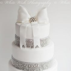 'Love thy CAKE' design Bling, glamour, crystal,  bow with brooch cake. Simple elegant striking cake. Wedding cake.