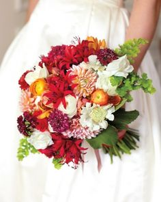 This bridal bouquet overflows with blooms, including dahlias, tulips, ranunculus, maiden-hair fern, nerines, scabiosa, and viburnum foliage.