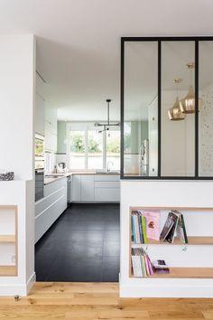 Une verrière d'atelier ouvre la cuisine sur l'entrée