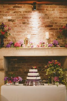 french fancy. jewel tones & jam jars for a creative wedding at le petit chateau. White wedding cake with purple ribbon.   Image by Gavin Forster Photography.  Read more: http://bridesupnorth.com/2017/01/12/french-fancy-jewel-tones-jam-jars-for-a-creative-wedding-at-le-petit-chateau-katie-david/  #wedding #cake #flowers