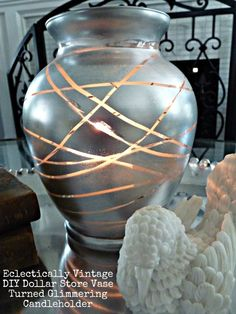 Mercury Glass Vase DIY  Supplies:  * Ugly glass vase (on hand but can find at Dollar Store – $1)  * Rubber bands (on hand from my girls giant rubber band ball)  * Spray paint (on hand but around $6 with Michael's coupon – I used Rustoleum Metallic Silver – $6)  * Candle (on hand – but you guessed it, Dollar Store – $1)