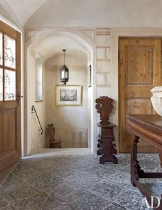 Seventeenth-century Italian furnishings outfit a stone-paved entrance hall in Saint Moritz, Switzerland; the staircase lantern is 18th-century Venetian - Studio Peregalli
