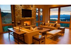 Interior view of the living room at twilight with expansive views onto the lake and mountains beyond. Contemporary house situated on a steep mountain slope. Wood siding, glu-lam beams, stone veneer, rusted corrugated metal shed roofs, and shingle gable roofs.