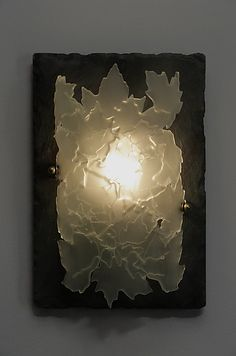 Leaflight by Rick Melby. Sconce created from *fused glass* leaves, cut by water-jet technology. After fusing, the glass is *etched:etched glass*, then *slumped:slumped glass* over a mold in a kiln. Glass is mounted on a sealed slate back, which is attached to a wood back board. Each sconce is unique, due to variations in composition and kiln firings. Signed on the back of mounting board. To clean, simply wipe glass or slate with a damp cloth. Sconce uses one incandescent bulb, candelabra ...