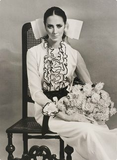 Fashion photograph by Bruno Benini of model Maggi Eckhardt seated on antique chair wearing a white Ninette dress, 1968