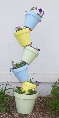 Garden Potted Plant Stack Idea  ------- I can have the kids work together to build one of these. Just need a metal rod and pots. However I dunno what to plant them with =(