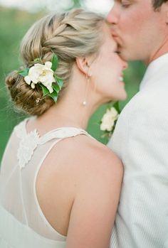 Moño con trenza y flor blanca - Peinados de novia