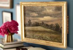One Kings Lane shares how a vintage oil painting, mounted on hinges, is an attractive way to camouflage things you don't want to see, but still need easy access to in your entryway, like alarm panels.