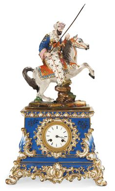 A PARIS PORCELAIN FIGURAL MANTEL CLOCK  MID-19TH CENTURY, PROBABLY JACOB PETIT  The clock case moulded with gilt scrolls and acanthus, surmounted by a Turk on a rearing dapple grey horse, holdinG a spear in his right hand, on grassy rectangular mound base