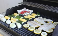 grilled tilapia + summer veggies. lining the grill with lemons is a great trick for grilling flaky fish! spotted on lovely renee's blog.