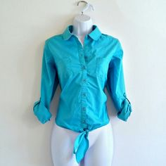 "$16. Retails at $44. (243) Aqua Blue Button Down Top - Size S -Crisp classic button down blouse in excellent condition, in a bold aqua blue. Tie at bottom. Sleeves can be rolled and cuffed with button tab. Bright and versatile. Bust - 38.5"" Waist - 38.5"" Length - 20"" Size - Small (PLEASE CHECK MEASUREMENTS) Label - Zac & Rachel Materials - Cotton, polyester, spandex Color may vary slightly. #zacandracheltop #zacandrachel #blue #aqua #buttondown #longsleeve #buttonup #bluebuttondown…"