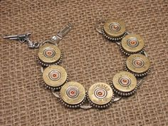 Materials: Winchester 28 guage shotgun shell casings, bracelet form, beaded edge settings, jump ring, gun charm.