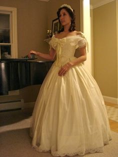 A pale yellow silk ballgown with a sheer lace trimmed overlay. Her off-the-shoulder bertha collar and large centered trim design are some of the main elements of a 1860's ball or evening gown.