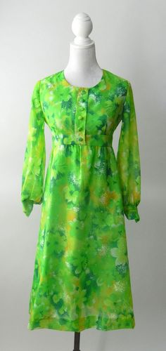 Vintage 1960s green nylon chiffon dress. Lined in matching green rayon except for sleeves, this has front decorative buttons and back nylon zipper. Sleeves end in button cuffs ad no maker's label. Siz