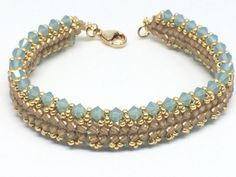 Evoking images of ocean waves and mermaids. this gorgeous bracelet features Swarovski Pacific Opal crystals, opaque gold lined seed beads, gold seed bead picots and a gold filled lobster clasp.  This beautiful bracelet is double sided and is the original design of Margherita Fusco.   Length is 7 1/2.