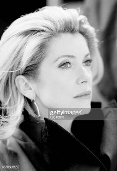 French actress Catherine Deneuve is illuminated by lightning during a storm at Cafe Marly near the Louvre museum