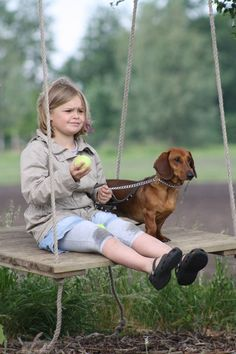Dachshund and little girl swinging.  National Dogs by Romana van Dongen-Lutt
